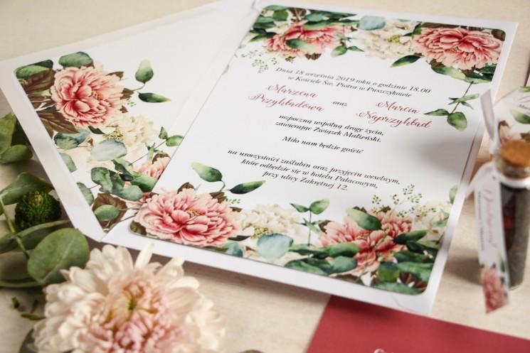 Białe zaproszenia ślubne z dodatkiem różowych i białych piwonii w otoczeniu liści eukaliptusa