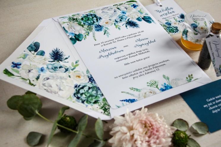 Niebieskie zaproszenia ślubne białymi różami z dodatkiem zielonych i niebieskich liści