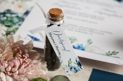 Podziękowania dla Gości w postaci buteleczek z herbatą, przywieszka z białymi różami z dodatkiem zielonych i niebieskich liści