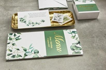 Menu weselne z zielonymi liśćmi eukaliptusa oraz złoceniem na okładce