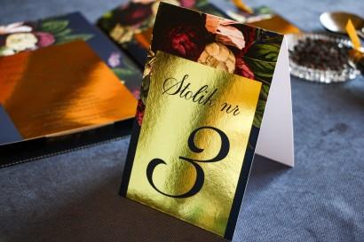 Złocone numery stolików weselnych, granatowa grafika z dodatkiem bukietu burgundowych i różowych kwiatów