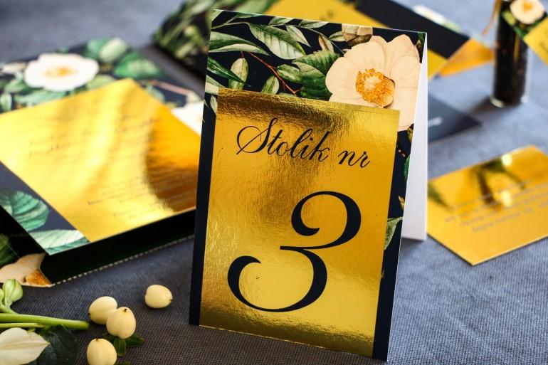 Złocone numery stolików weselnych, granatowa grafika z białą kamelią i dodatkiem zielonych liści
