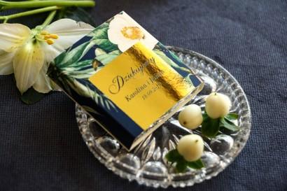 Podziękowanie dla gości weselnych w postaci czekoladki. Złota, granatowa owijka z białą kamelią i dodatkiem zielonych liści