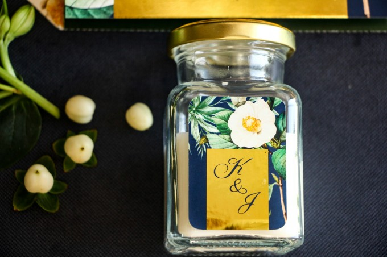 Świeczki - podziękowania dla gości weselnych w stylu Glamour. Złocona, etykieta z białą kamelią i dodatkiem zielonych liści