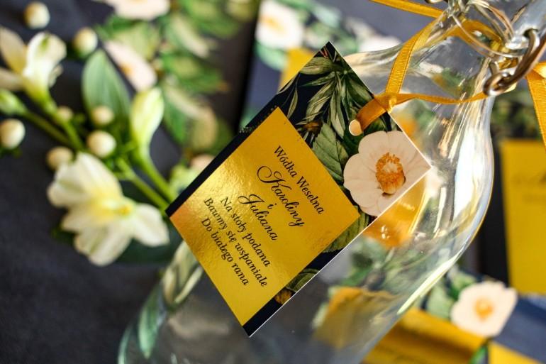 Złote zawieszki na butelki weselne w stylu Glamour. Granatowa grafika z białą kamelią i dodatkiem zielonych liści
