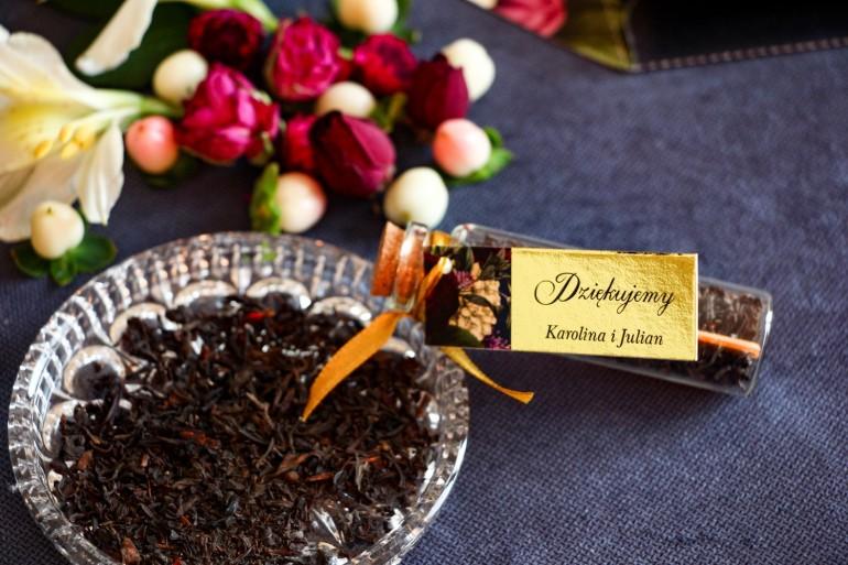 Podziękowania dla Gości w postaci buteleczek z herbatą. Złota przywieszka z dodatkiem bukietu burgundowych i różowych kwiatów