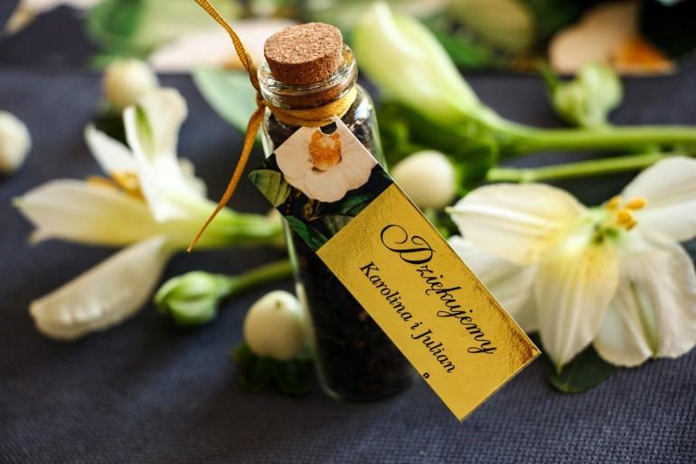 Podziękowania dla Gości w postaci buteleczek z herbatą. Złota przywieszka z białą kamelią i dodatkiem zielonych liści
