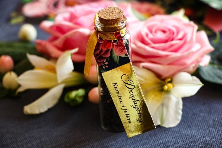 Podziękowania dla Gości w postaci buteleczek z herbatą. Złota przywieszka z różowymi piwoniami i różami
