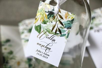 Biało-zielone zawieszki na butelki weselne ze złoconymi gałązkami w stylu glamour, motyw delikatnych, białych kwiatów i zieleni