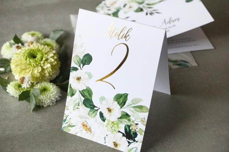 Biało-zielone Numery stołów weselnych ze złoconymi gałązkami w stylu glamour, motyw delikatnych, białych kwiatów i zieleni