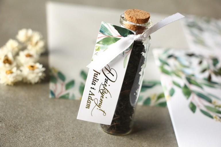 Podziękowania dla Gości w postaci buteleczek z herbatą. Przywieszka z konwalią i złoconymi gałązkami w stylu glamour