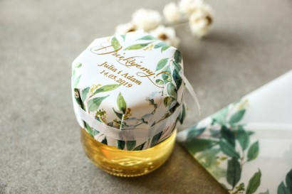 Słoiczek z miodem - słodkie podziękowanie dla gości weselnych. Biało - zielony kapturek ze złoconymi napisami z konwalią