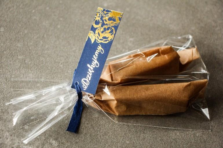 Podziękowania dla Gości w postaci słodkich Krówek. Granatowa przywieszka ze złoceniem grafiki róż