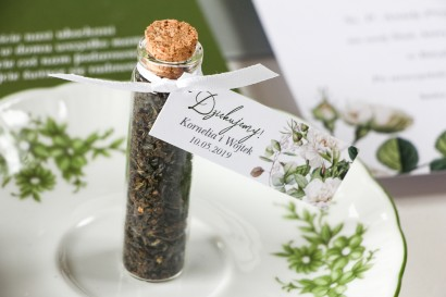 Podziękowania dla Gości w postaci buteleczek z herbatą, przywieszka z białymi różami i delikatnymi zielonymi gałązkami
