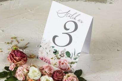 Różowe Numery stolików weselnych z różami i delikatnymi białymi hortensjami oraz z zielonymi gałązkami