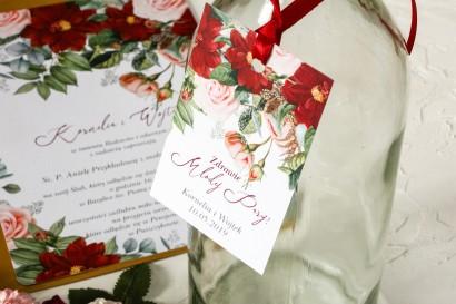 Zawieszki na butelki weselne z bordowymi daliami i pastelowymi różami, całość w otoczeniu zieleni