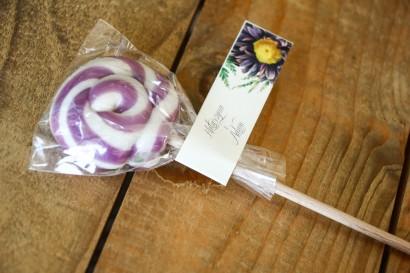 Lizaki - słodkie podziękowania dla gości weselnych. Przywieszka astrami w odcieniach fioletu oraz gałązkami paproci