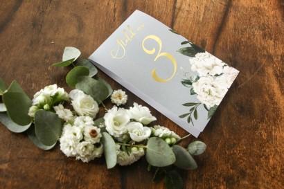 Szare Numery stolików weselnych ze złoceniem w stylu Glamour z białymi piwoniami i zielonymi gałązkami