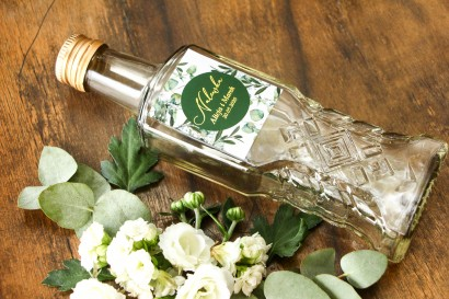 Butelki na nalewki wraz z etykietą z eukaliptusem i gipsówką. Etykiety nawiązują do motywu greenery oraz glamour