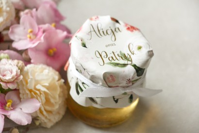 Słoiczek z miodem - podziękowanie dla gości weselnych. Kapturek ze złoconymi napisami oraz z pudrowymi, różowymi kwiatami róży