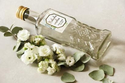 Butelki na nalewki wraz z etykietą w stylu glamour z białymi różami i piwoniami