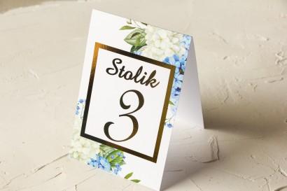Złocone Numery stolików ślubnych z niebieską i białą hortensją w otoczeniu zieleni