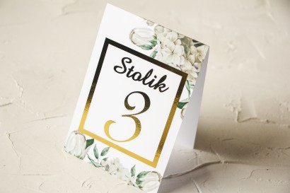 Złocone Numery stolików ślubnych z białą hortensją i tulipanami w otoczeniu zieleni