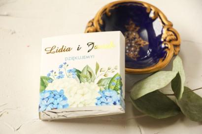 Podziękowanie dla gości weselnych w postaci mlecznej czekoladki, owijka ze złoconymi napisami oraz z niebieską i białą hortensją