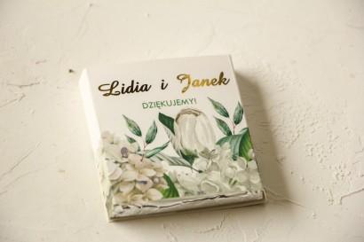 Podziękowanie dla gości weselnych w postaci mlecznej czekoladki, owijka z białą hortensją i tulipanami