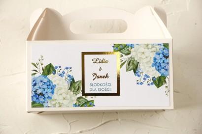 Prostokątne Pudełko na ciasto weselne ze złoceniami oraz z niebieską i białą hortensją w otoczeniu zieleni