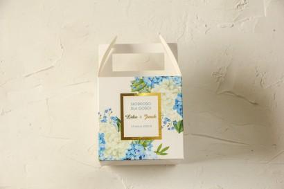 Kwadratowe Pudełko na ciasto weselne ze złoceniami oraz z niebieską i białą hortensją w otoczeniu zieleni
