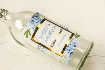 Złocone Etykiety samoprzylepne na butelki na alkohol z niebieską i białą hortensją w otoczeniu zieleni