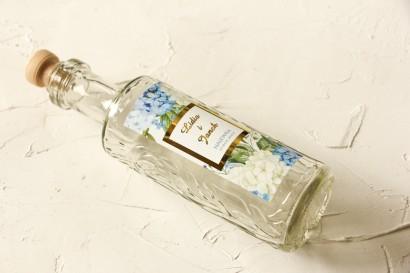Butelki na nalewki wraz ze złoconą etykietą oraz z niebieską i białą hortensją w otoczeniu zieleni