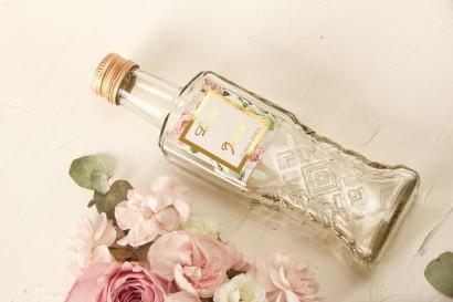 Butelki na nalewki wraz ze złoconą etykietą oraz z różowymi piwoniami w towarzystwie białych róż i zieleni