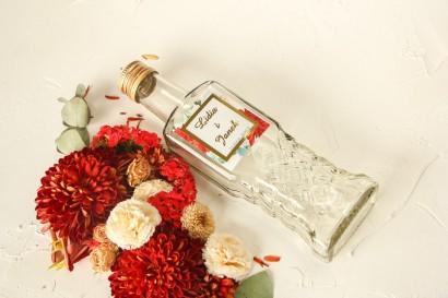 Butelki na nalewki wraz ze złoconą etykietą oraz z bordowymi i białymi różami