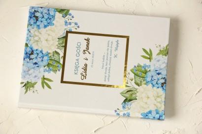 Ślubna Księga Gości ze złoceniami z niebieską i białą hortensją w otoczeniu zieleni