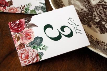 Ślubne Numery stolików weselnych z różowym bukietem i zielonymi gałązkami