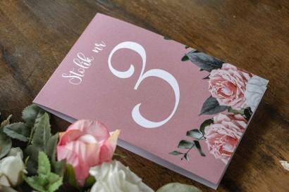 Numery stolików weselnych w kolorze pudrowego różu. Na numerze kompozycja z białych i różowych piwonii i róż