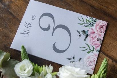 Numery stolików weselnych w kolorze szarym. Na numerze kompozycja z białych i pastelowych róż