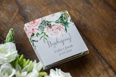 Podziękowanie dla gości weselnych w postaci mlecznej czekoladki, szara owijka z kompozycją kwiatową z białych i pastelowych róż.