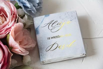 Podziękowanie dla gości weselnych w postaci mlecznej czekoladki. Marmurkowa, złocona owijka w pastelowym, niebieskim kolorze