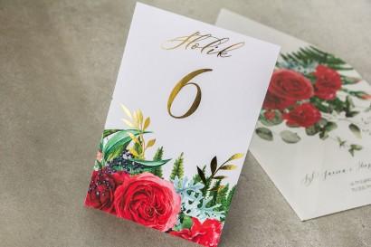 Numery stołów weselnych ze złotymi gałązkami i bordowymi różami z dodatkiem czerwonych goździków i eukaliptusa.